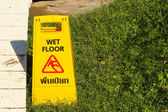 Yellow sign warning for wet floor at the park — Stock Photo