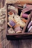 Wooden box with laces, ribbons and threads — Stock Photo