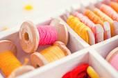 Colección de amarillo, rojo, rosa bobinas de hilos dispuestos en una caja de madera blanca — Foto de Stock