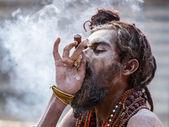 A Hindu sadhu smoking a hash pipe - India. — Stock Photo