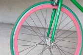 Wheel of green fixed gear bicycle at building — Stock Photo
