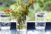 Flowers in glass jar with bokeh background — Stock Photo
