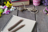 Still life of note book around nice flowers on wooden table — Stock Photo