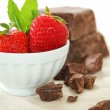 Brown chocolate chunk block and fresh cut strawberries. This is perfect harmony of tasting flavor chocolate and strawberry for cake,  ice cream, fondue, desserts. Brown chocolate chunk strawberries. — Stock Photo #72329107