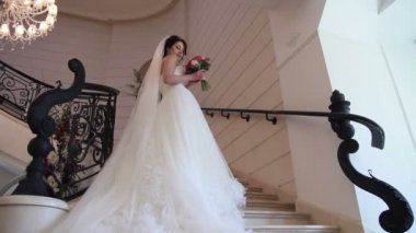 Bride with bouquet posing near the window on stairs — Stock Video