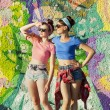 Two young girls stand in the background of graffiti and look out for something — Stock Photo #67395655