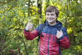 The guy with the backpack hiking in the forest. Young man showing thumb up — Stock fotografie