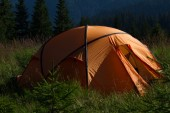Tent  overlooking mountains and fir trees — Stock Photo
