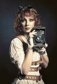 Beautiful steampunk girl with old camera — Stock Photo
