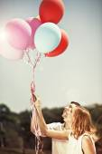 Young happy couple holding colorful ballons and smiling — Stock Photo