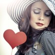 Beautiful elegant woman in hat holding heart in her hands and sm — Stock Photo #63566667