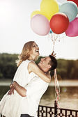 Young attractive happy couple with colorful ballons embracing an — Stock Photo