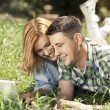 Happy young couple lying on the grass, looking at laptop and smi — Stock Photo #67802849
