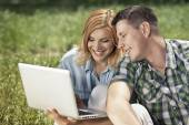 Cheerful young couple sitting on the grass, looking at laptop an — Stock fotografie