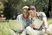 Young attractive couple sitting on the grass, looking at laptop  — Stok fotoğraf
