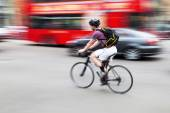 Bicycle rider overtaking a Porsche and a London bus — Stock Photo