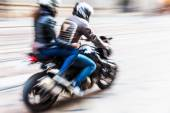 Motorcycle rider with pillion passenger with motion blur — Stock Photo