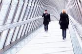 Business people walking on a footbridge — Stock Photo