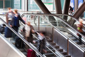 People in motion blur on an escalator — 图库照片