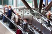 People in motion blur on an escalator — Stock Photo