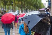 Pedestrians with rain umbrella in the rainy city — Stock Photo