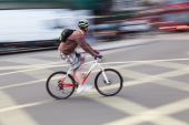 Cyclist in motion blur in the city traffic — Stock Photo