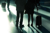 Traveling people with trolley bags at the airport in backlit — Stock Photo