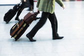 Urgent people with trolley bags at the airport — Stock Photo