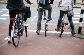 People with bicycles waiting at the street crossing — Stock Photo