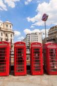 Four traditional red phone boxes in a row in London with a Metro sign in London, UK — Stock Photo