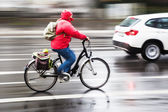 Cyclist in city traffic in motion blur on a rainy day — Стоковое фото