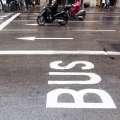 Bus lane of a city street with scooterists in the background — Foto Stock