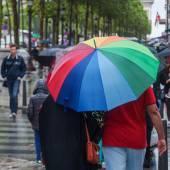 Colorful rain umbrella on the busy sidewalk — Stock Photo