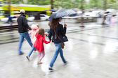 Family in motion blur walking in the rainy city — Stock Photo