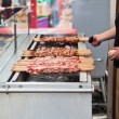 Food stand with skewers on a grill on a city festival — Stock Photo #54714469