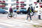 City traffic scene with cars, cycles and pedestrians — Stock Photo
