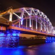 Blue illuminated railroad bridge over the river Daugava in Riga, Latvia — Stock Photo #54935419