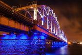 Blue illuminated railroad bridge over the river Daugava in Riga, Latvia — Stock Photo