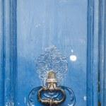 Old blue door with an antique doorknocker — Stock Photo #55035133