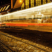 Tram in motion blur at the market halls in Riga, Latvia, at night — Stock Photo