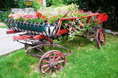 Antique and picturesque trailer decorated with flowers — Stock Photo