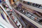 Escalators in a shopping mall with people in motion blur — Stock Photo