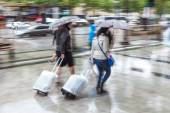 Women with trolleys and rain umbrellas walking in the rainy city — Stock Photo