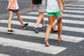 Summery clothed people crossing the street at the pedestrian crossing — Stock Photo