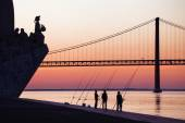 Silhouettes of anglers at the Tagus River in Lisbon, Portugal, before sunset — Stock Photo