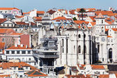 Roofs of Lisbon, Portugal, with an old church ruin, the elevator Santa Justa and unidentified people — Photo