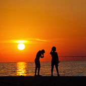 Silhouettes of angling children at the sea at sunset — Stock Photo