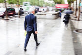 Businessman walking in the rainy city in motion blur — ストック写真
