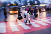 People crossing a street at a bus terminal — Stock Photo