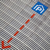 Parking sign and an arrow at a corrugated sheet metal facade — Foto Stock